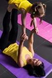 年轻与做飞行战士姿势的一个学龄女儿一起的母亲实践的瑜伽说谎在席子 免版税图库摄影