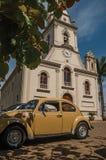 与停放的汽车和常青树庭院的教会门面在São曼纽尔的一个晴天 库存照片