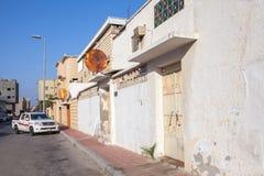 与停放的汽车和白色墙壁,沙特阿拉伯的普通的街道视图 图库摄影