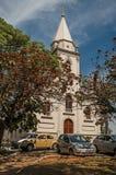 与停放的汽车的教会门面和常青庭院在São曼纽尔的一个晴天 库存照片
