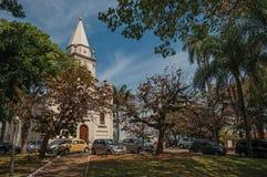 与停放的汽车的教会门面和常青庭院在São曼纽尔的一个晴天 免版税库存图片