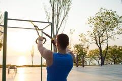 与停止皮带的锻炼在室外健身房、大力士训练及早在公园的早晨的,日出或者日落在海 图库摄影