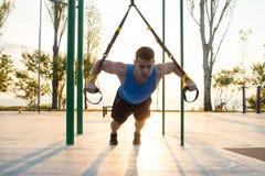 与停止皮带的锻炼在室外健身房、大力士训练及早在公园的早晨的,日出或者日落在海 库存照片