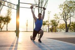 与停止皮带的锻炼在室外健身房、大力士训练及早在公园的早晨的,日出或者日落在海 库存图片