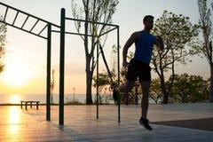 与停止皮带的锻炼在室外健身房、大力士训练及早在公园的早晨的,日出或者日落在海 免版税库存照片