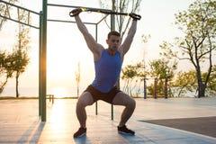 与停止皮带的锻炼在室外健身房、大力士训练及早在公园的早晨的,日出或者日落在海 免版税库存图片