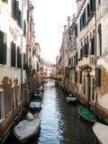 与停泊小船的狭窄的运河区域在威尼斯 库存图片