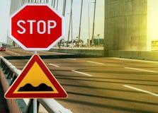 与停车牌的红色和黄色三角警告路标前面坎坷的路的警告 库存照片