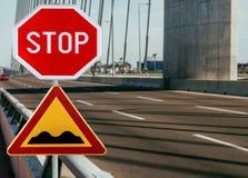 与停车牌的红色和黄色三角警告路标前面坎坷的路的警告 免版税库存照片