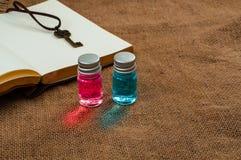 与健康和马娜不可思议的液体的两小玻璃魔药在粗麻布报道表面并且打开空的葡萄酒笔记薄 库存照片