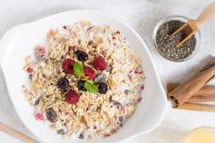 与健康早餐Muesli的晴朗的早晨用牛奶、Chia种子、莓果和桂香 免版税库存图片