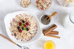 与健康早餐Muesli的晴朗的早晨用牛奶、Chia种子、莓果和桂香 库存图片