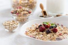 与健康早餐Muesli的晴朗的早晨用牛奶、Chia种子、莓果和桂香 免版税库存照片