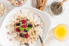 与健康早餐Muesli的晴朗的早晨用牛奶、Chia种子、莓果和桂香 图库摄影