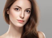 与健康皮肤的年轻美丽的妇女面孔画象在灰色背景 免版税库存照片