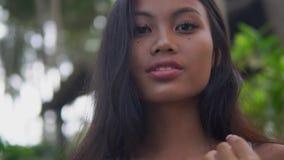 与健康黑暗的皮肤和黑色头发的年轻东方模型反对绿色植物 股票录像