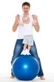 与健身球的愉快的家庭。 免版税图库摄影