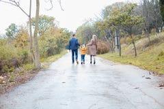 与儿子的一个家庭在路在雨中去 免版税库存照片