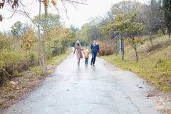 与儿子的一个家庭在路在雨中去 免版税库存图片