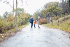 与儿子的一个家庭在路在雨中去 库存照片