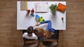 与儿子的年轻母亲绘画,在桌,做家庭作业顶面射击木条地板木地板的孩子后的开会 股票视频