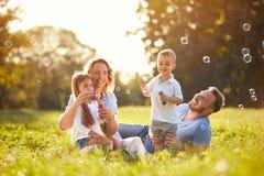 与儿童打击肥皂泡的家庭 图库摄影