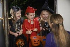 与儿童把戏或款待的万圣夜党在服装 免版税库存图片