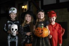 与儿童把戏或款待的万圣夜党在服装 免版税库存照片