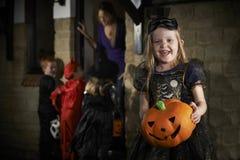 与儿童把戏或款待的万圣夜党在服装 免版税图库摄影