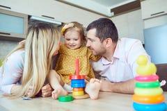 与儿童游戏坐在桌上的棋的一个家庭 图库摄影