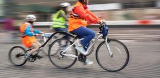 与儿童的乘驾的年轻家庭在城市街道上的自行车 库存图片