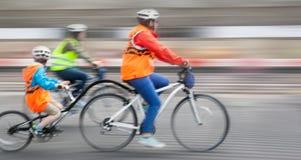 与儿童的乘驾的年轻家庭在城市街道上的自行车 图库摄影