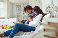 与儿童看书的家庭 图库摄影
