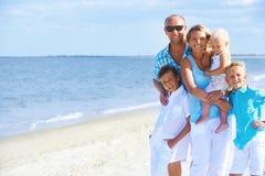 与儿童站立的愉快的微笑的家庭 库存照片