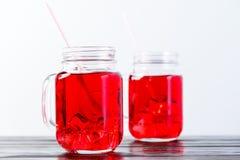 与充分两个金属螺盖玻璃瓶的木台式在光b的柠檬水 免版税图库摄影