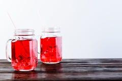 与充分两个金属螺盖玻璃瓶的木台式在光b的柠檬水 免版税库存照片