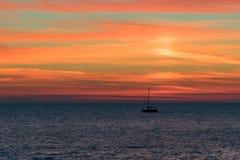 与充满活力的日落的海景在风平浪静和一条浮动小船 免版税库存图片