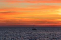 与充满活力的日落的海景在风平浪静和一条浮动小船 库存图片