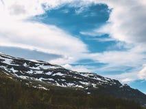 与充满活力的蓝色狡猾和白色云彩的一座北欧下雪的山 库存照片