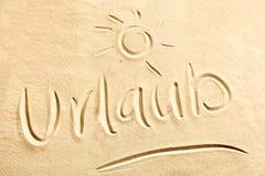 与光亮的太阳的Urlaub文本在海滩沙子 免版税库存图片