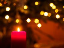 与光亮的星的火焰状蜡烛在背景 免版税库存照片
