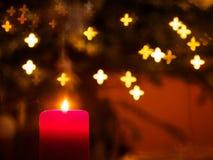 与光亮的星的火焰状蜡烛在背景 库存图片