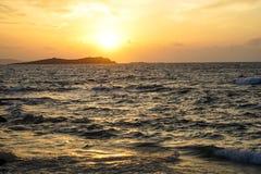 与光反射和宽橙色颜色天空背景美丽的树荫的日落风景强有力的有风移动的海波浪视图  免版税库存照片