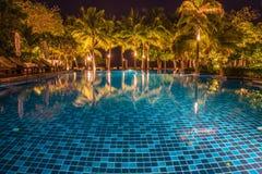 与光反射的蓝色游泳池在晚上 免版税库存照片