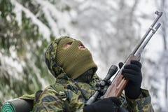 与光学步枪的猎人在冬天 图库摄影
