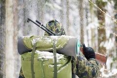 与光学步枪的猎人在冬天 免版税库存照片