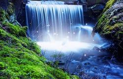 与光的不可思议的童话瀑布在森林 免版税库存图片