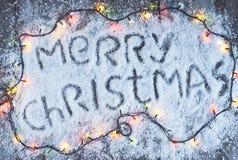 与光的圣诞快乐手拉的字法在木委员会 免版税库存图片