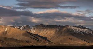 与光的布朗山和阴影和剧烈的日落云彩 图库摄影