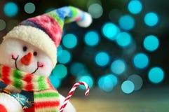 与光的滑稽的雪人在背景中 新年好 免版税库存图片